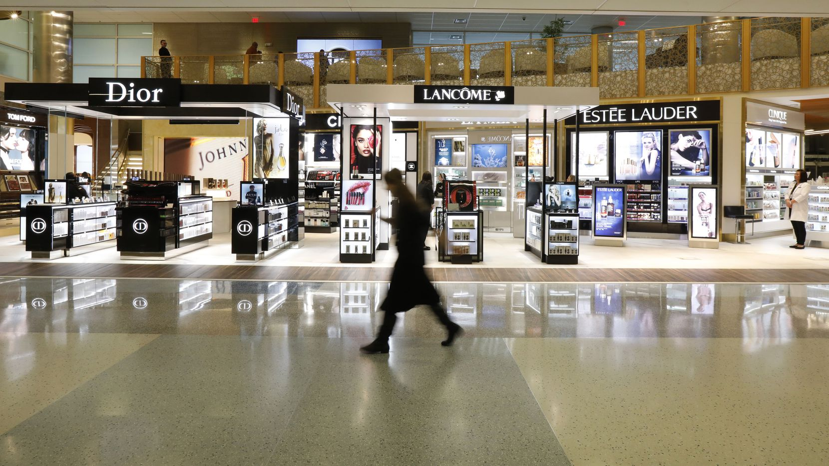 A passenger walks in front of the largest duty-free store in the Americas in Terminal D at DFW International Airport, featuring two levels, two elevators, four staircases, and extensive mezzanine lounge space in 17, 400 total square feet on Wednesday, December 20, 2017. (David Woo/The Dallas Morning News)