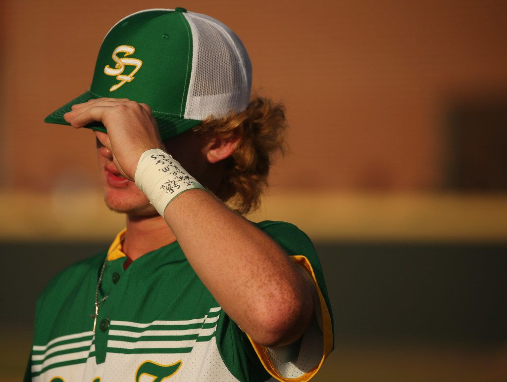 Santa Fe pitcher Rome Shubert, wearing the initials of some of the victims of the Santa Fee High School shooting on his wrist and who was also injured, stands near the dugout before the second game of the best-of-three series in the Class 5A Region III playoff high school baseball game between Santa Fe and Kingwood Park at Jim Kethan Field at Deer Park High School in Deer Park, TX Saturday May 19, 2018. On Friday morning, 10 people were killed and 13 were injured after a shooting at Santa Fe High School. The game was postponed to Saturday after it was scheduled for Friday. Dimitrios Pagourtzis was booked into the Galveston County Jail on capital murder charges.