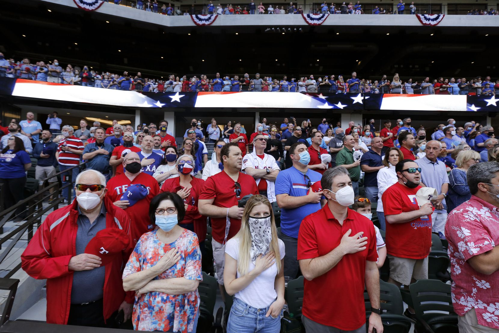 Texas Rangers fans (from left) Fred Aurbach, his girlfriend Leslie Lehman, his daughter-in-law Melissa Aurbach and son Wilson Aurbach and the rest of the nearly sold-out Opening Day crowd stand for the National anthem at Globe Life Field in Arlington, Monday, April 5, 2021. The Rangers were facing the Toronto Blue Jays in the home opener. (Tom Fox/The Dallas Morning News)