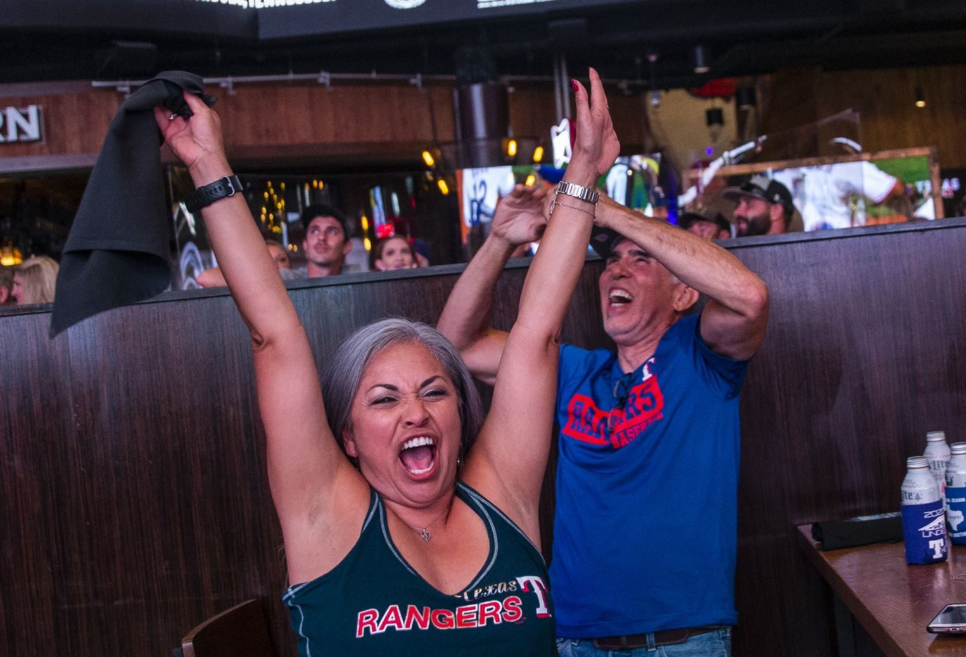 Claudia Borunda (left), from California, cheers with fans as the Texas Rangers win their opening day game of their season at Texas Live! in Arlington, Texas, on Friday, July 24, 2020. The Rangers played the Colorado Rockies at the new Globe Life Field stadium, but fans had to watch on televised screens outside due to the ongoing pandemic. (Lynda M. Gonzalez/The Dallas Morning News)