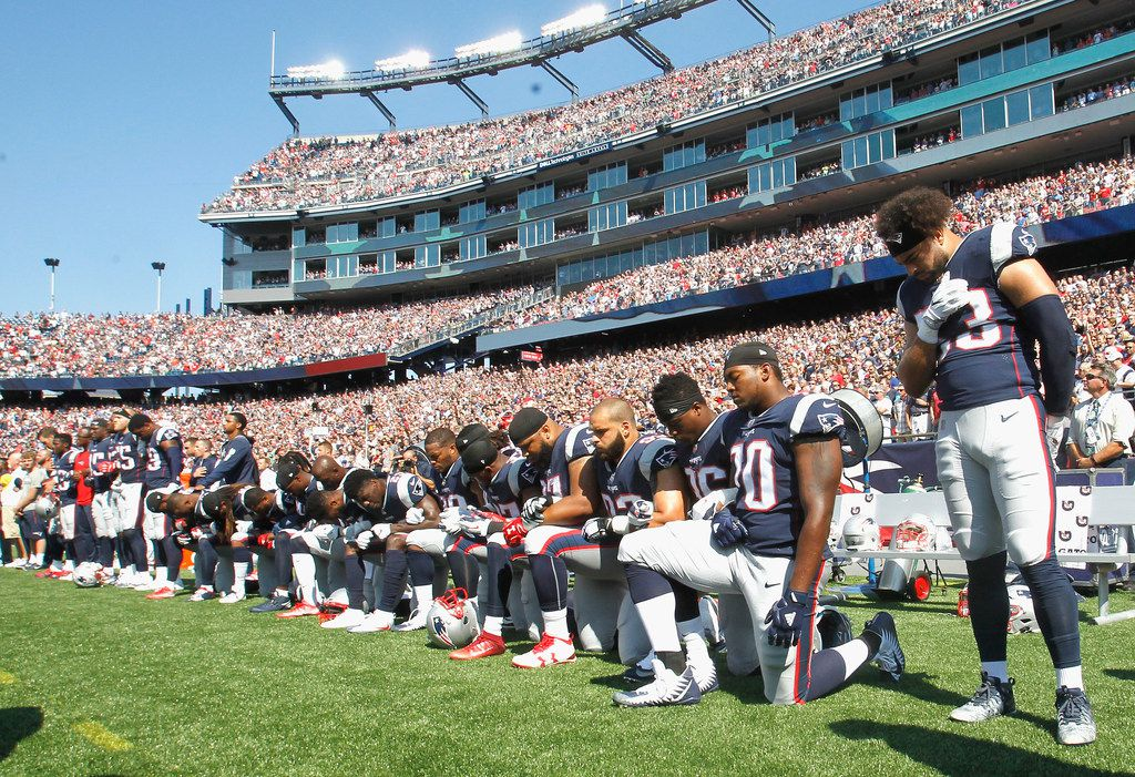 FOXBORO, MA - SEPTEMBER 24:  Members of the New England Patriots kneel during the National Anthem before a game against the Houston Texans at Gillette Stadium on September 24, 2017 in Foxboro, Massachusetts.  (Photo by Jim Rogash/Getty Images)