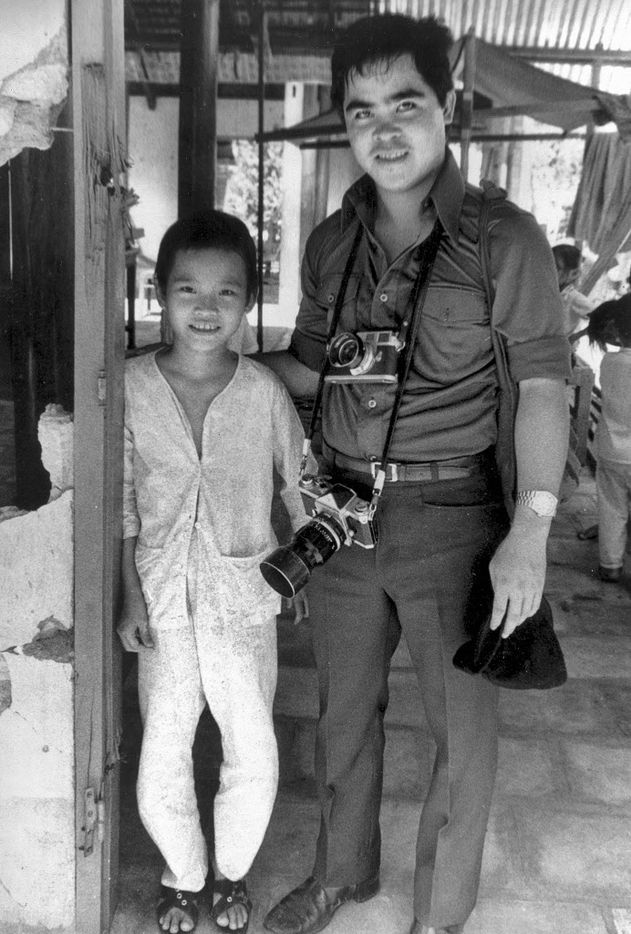 In this 1973 file photo, Phan Thi Kim Phuc, left, is visited by Associated Press photographer Nick Ut at her home in Trang Bang, Vietnam. As a 9-year-old, Kim Phuc was the subject of a Pulitzer Prize-winning photo by Ut as she fled in pain from a misdirected napalm attack against her village by South Vietnamese planes in 1972. After taking the photograph, Ut came to the girl's aid and transported her to a hospital.