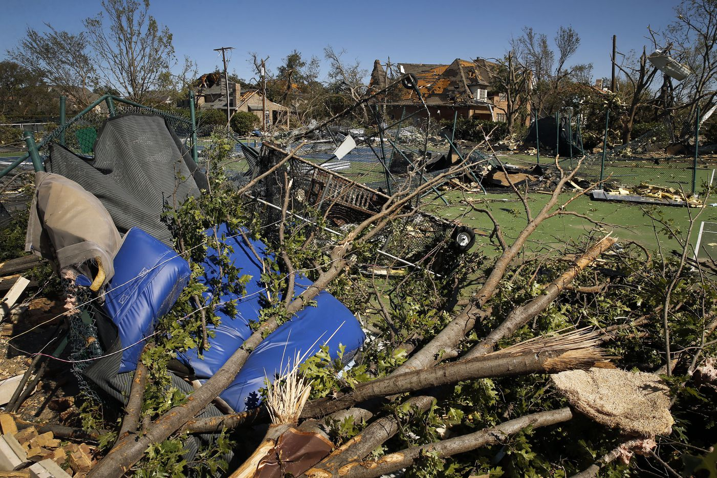 Parts of the St. Mark's School of Texas gymnasium, including the wall a handful of trees, destroyed the tennis courts during the tornado in Dallas, Monday, October 21, 2019. A tornado tore through the entire neighborhood knocking down trees and ripping roofs from homes. (Tom Fox/The Dallas Morning News)