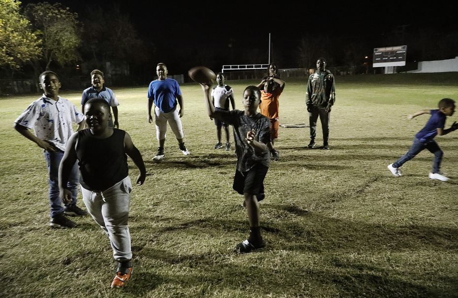 Javorian Simpson (center), 10, throws a pass on the football field at the Cedar Crest Community Center in Dallas on Nov. 24, 2020.