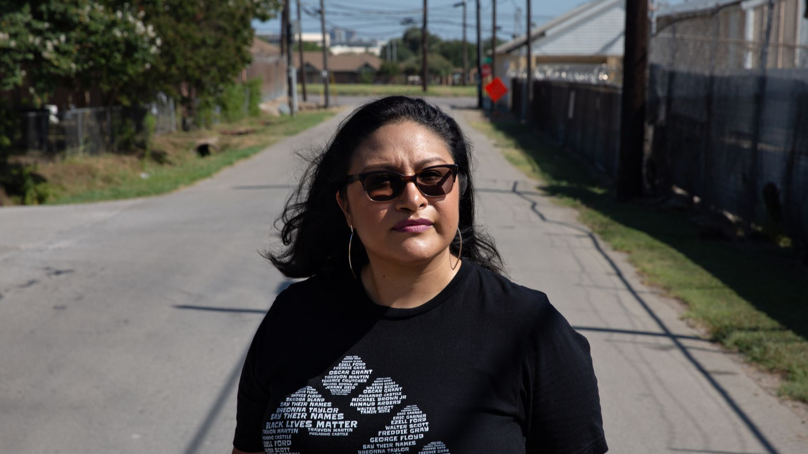 """Janie Cisneros stands for a portrait between her neighborhood and the GAF shingle manufacturing plant in Dallas on July 11, 2021. Janie is emerging as a leader in the fight against the air pollution the facility generates, which she believes affects lives and health of those living nearby.  """"It's happening right in front of me. How could I not say something?"""""""