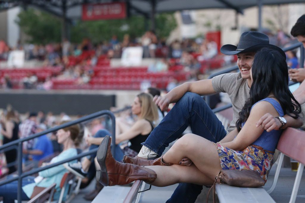 Jason Schiele and Jessica Rodriguez, both of Dallas, speak as Chris Young performs during the Off the Rails Country Music Fest at Toyota Stadium in Frisco. (Andy Jacobsohn/The Dallas Morning News)