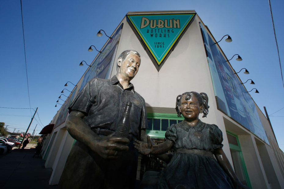 """A statue of W. P. """"Bill"""" Kloster handing a Dr Pepper to a girl, titled The Inspiration, stands in front of the old bottling business he owned in Dublin. (Guy Reynolds/Staff Photographer)"""