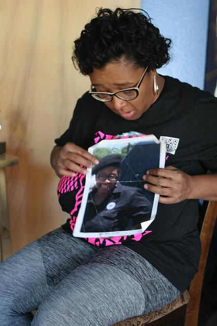 Olinka Green shows an photo of herself in her New Black Panther Party uniform from her early days in the organization.