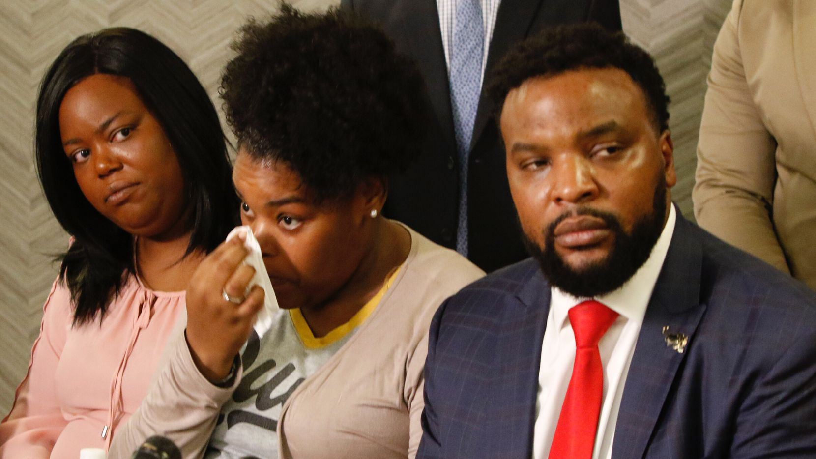 Amber Carr, center, wipes a tear as her sister, Ashley Carr, left, and attorney Lee Merritt, right, listen to their brother Adarius Carr talk about their sister, Atatiana Jefferson during a press conference at 1910 Pacific on Monday morning, October 14, 2019 in downtown Dallas. Atatiana Jefferson, a 28-year-old black woman, was shot and killed in her home by a white Fort Worth police officer during a welfare check.
