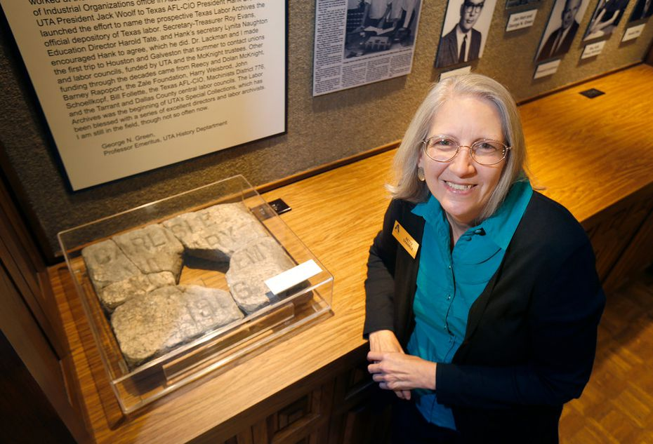 "University archivist Betty Shankle poses next to a broken marble marker with the inscription ""Carlisle Military Academy 1906"" in the University of Texas at Arlington Special Collections in the university library."