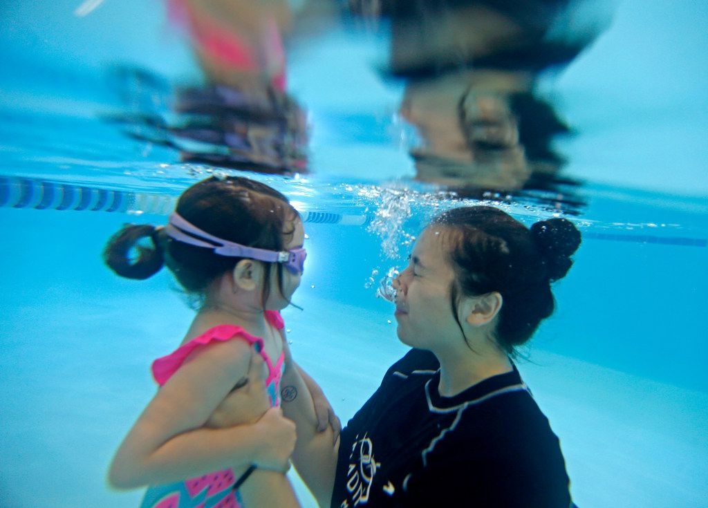 Olivia Lemmon, 2, gets a swim lesson to become comfortable underwater from instructor Monica Perez during a class at Jim Montgomery Swim School in Dallas. A major technique taught in the classes is how to go back to the wall of the pool.