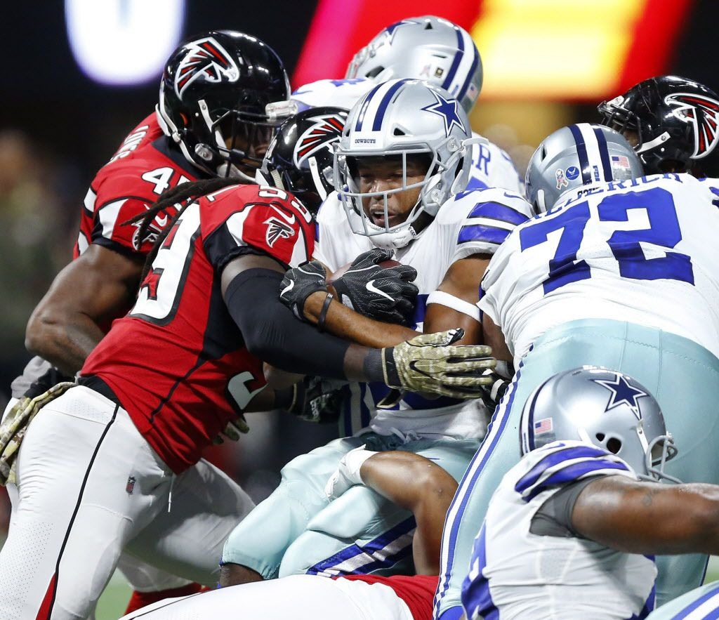 Dallas Cowboys running back Alfred Morris (46) is wrapped up by the Atlanta Falcons defense as he turns his back after running up the middle during the first quarter at Mercedes-Benz Stadium in Atlanta, Georgia, Sunday, November 12, 2017. (Tom Fox/The Dallas Morning News)
