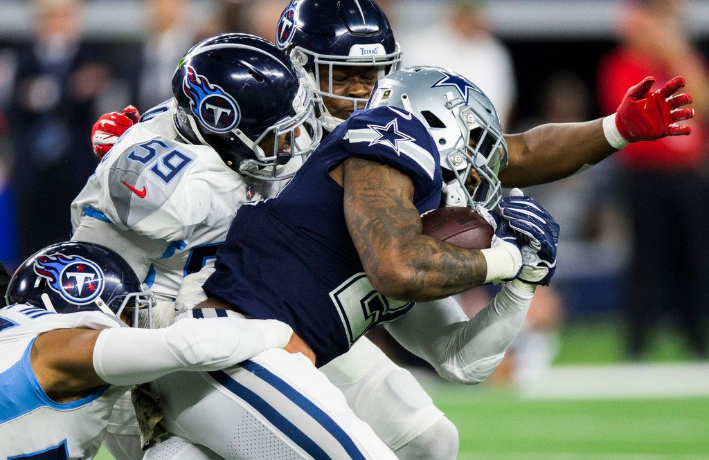 Dallas Cowboys running back Ezekiel Elliott (21) is tackled by Tennessee Titans defenders during the second quarter of an NFL game between the Dallas Cowboys and the Tennessee Titans on Monday, November 5, 2018 at AT&T Stadium in Arlington, Texas. (Ashley Landis/The Dallas Morning News)