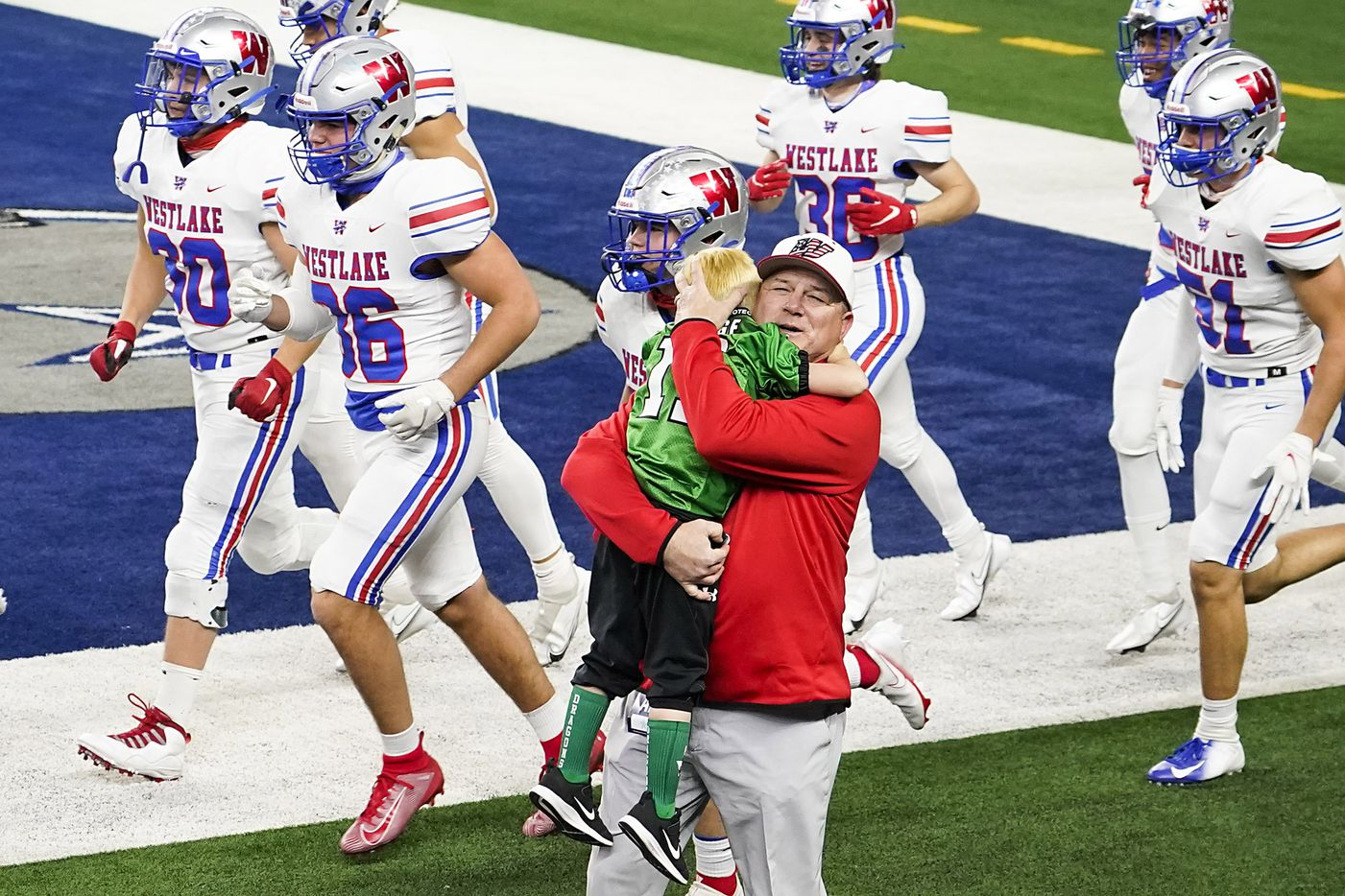 Austin Westlake head coach Todd Dodge hugs his grandson Tate, 5, as his team takes the field to warm warm up before facing his son, Southlake Carroll head coach Riley Dodge, in the Class 6A Division I state football championship game at AT&T Stadium on Saturday, Jan. 16, 2021, in Arlington, Texas.