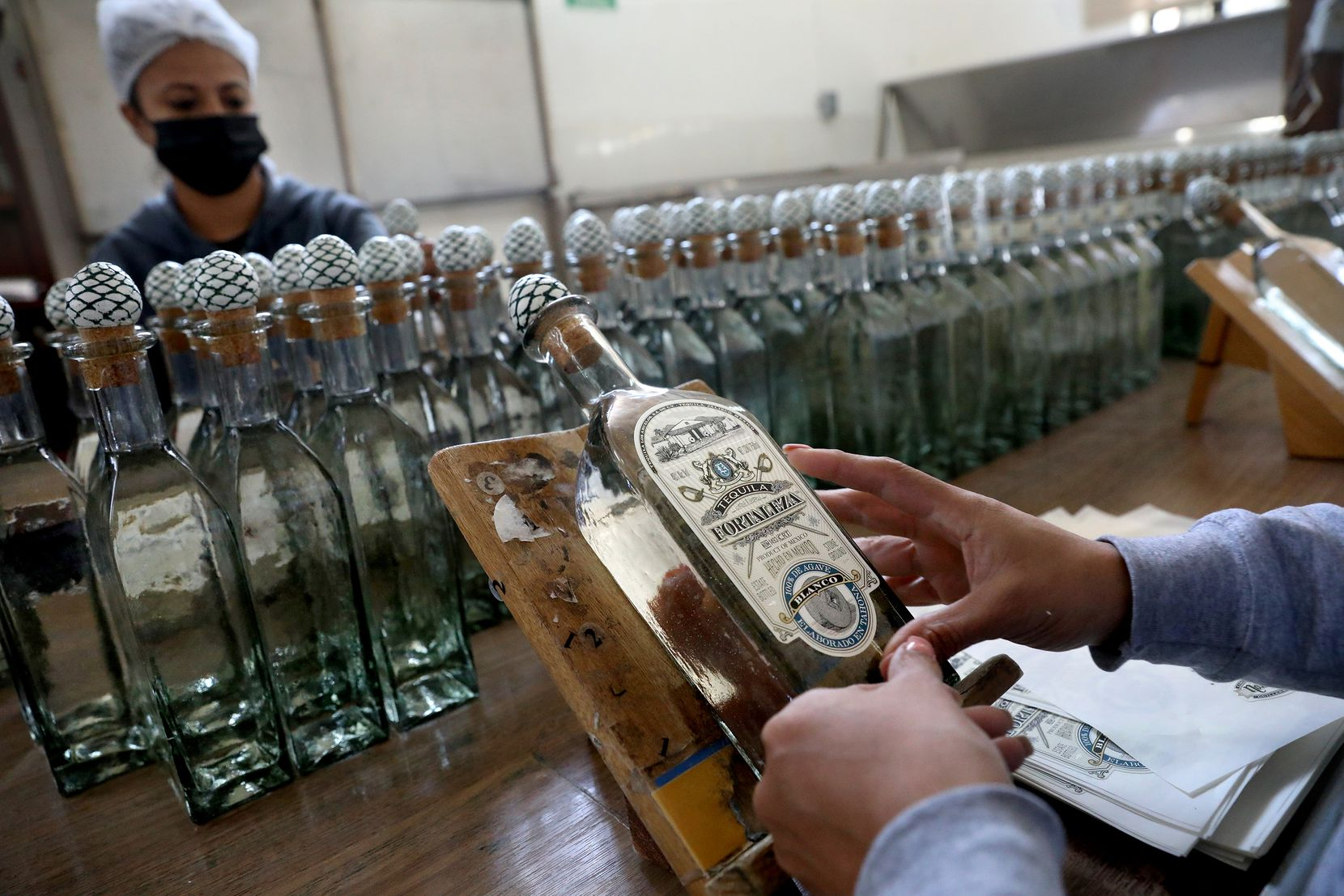 Workers place labels by hand on bottles of tequila at the Fortaleza tequila distillery on July 26 in Tequila, Jalisco.