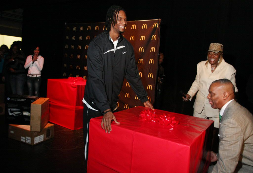 In 2010, Chris Bosh (center), his father, Noel Bosh, and mother, Freida Bosh, delivered gifts to his alma mater, Lincoln High School in Dallas.