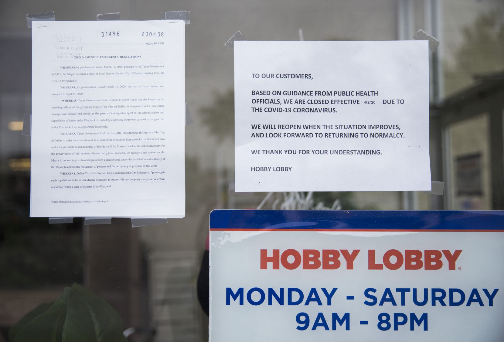 Signs are posted at the front entrance of Hobby Lobby on Preston Road in Dallas.