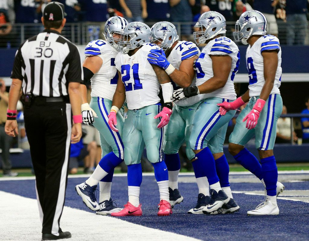 Back judge Todd Prukop (30) watches as Dallas Cowboys' Ezekiel Elliott, celebrates his touchdown run with Zack Martin (70), Travis Frederick (72), Ronald Leary (65) and Brice Butler (19) in the first half of an NFL football game against the Cincinnati Bengals on Sunday, Oct. 9, 2016, in Arlington, Texas. (AP Photo/Ron Jenkins)