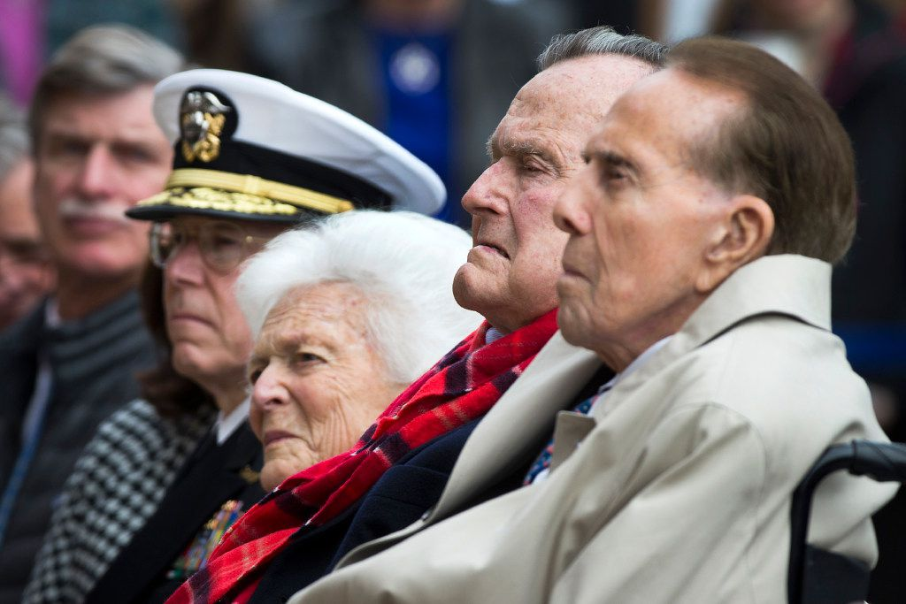 Former President George H. W. Bush and former Senator Bob Dole sit with Barbara Bush and Admiral Chip Miller, former commanding officer of the USS George H.W. Bush, during a Pearl Harbor 75th Anniversary commemoration at the George Bush Presidential Library on Wednesday, Dec. 7, 2016, in College Station, Texas. (Smiley N. Pool/The Dallas Morning News)