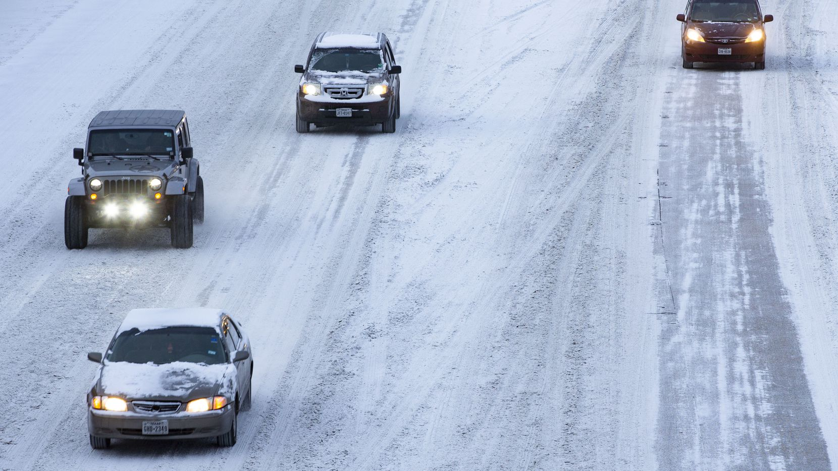 Snow covers cars and the road on US 75 heading out of Downtown Dallas on Monday morning.