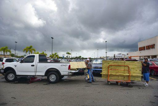 Hombres cargando tablones de madera para proteger las ventanas antes de la llegada del huracán Irma, en Carolina, Puerto Rico, el martes 5 de septiembre de 2017. (AP Foto/Carlos Giusti)
