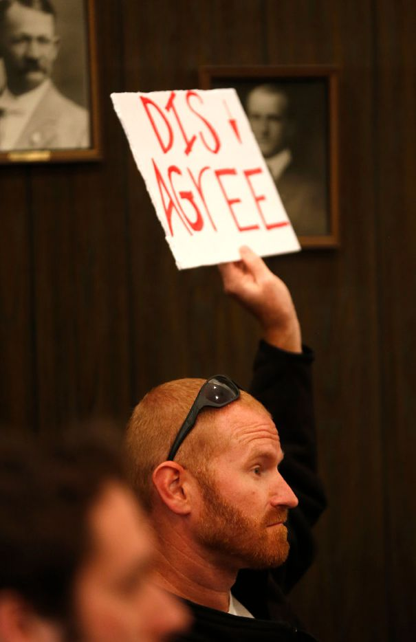 Justin Snider holds up a sign at Rep. Joe Barton's town hall meeting at Corsicana Government Center in Corsicana on Tuesday. Barton answered questions on a variety of topics including a health care plan during the Q&A session. (Jae S. Lee/The Dallas Morning News)
