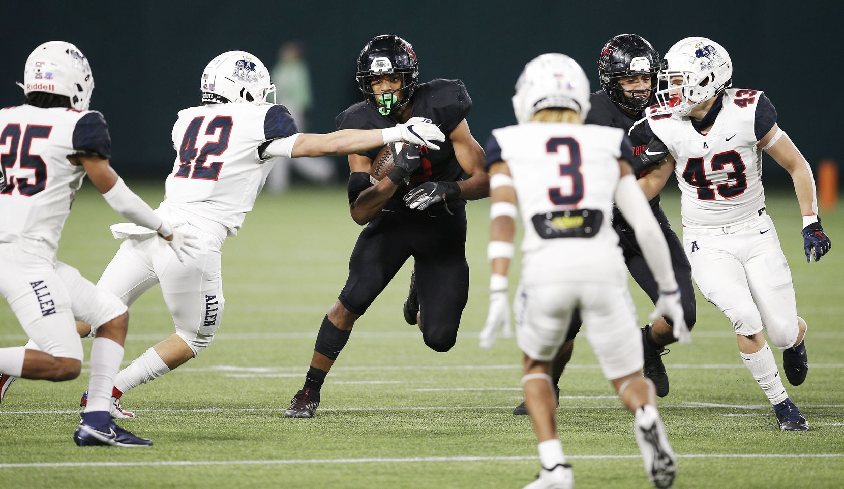 Euless Trinity junior running back Ollie Gordon, center, looks for room against the Allen defense during the first half of a high school Class 6A Division I Region I semifinal football game at Globe Life Park in Arlington, Saturday, December 26, 2020. (Brandon Wade/Special Contributor)