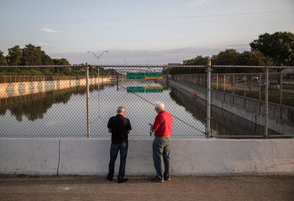 Lance Leibole, left, and John Lee take pictures of a portion of the Sam Houston Tollway in Houston that remains submerged under floodwaters, Aug. 31, 2017. As what was once a Category Four hurricane weakened into a tropical depression, a region that had been incapacitated by the storm continued to gather itself Thursday and take stock of damage that officials say will take years to repair. (Tamil Kalifa/The New York Times)