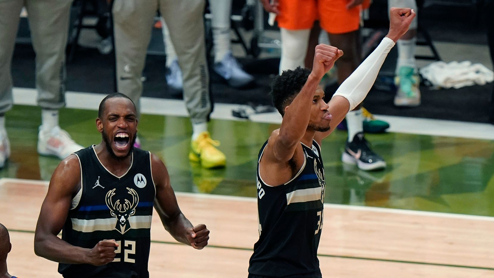 Milwaukee Bucks forward Khris Middleton (22) and forward Giannis Antetokounmpo reacts as time expires during the second half of Game 6 of basketball's NBA Finals against the Phoenix Suns in Milwaukee, Tuesday, July 20, 2021. The Bucks won 105-98. (AP Photo/Paul Sancya)
