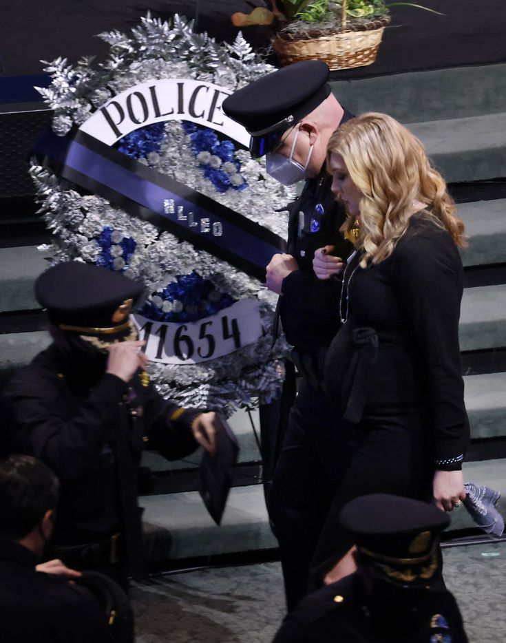 Noel Bergenske Penton (right) is escorted from her husbands funeral service at Prestonwood Baptist Church in Plano, Texas, Monday, February 22, 2021. Her husband, Dallas Police officer Mitchell Penton, was killed, Saturday, Feb. 13, 2021, in a crash involving a drunk driving suspect. (Tom Fox/The Dallas Morning News)