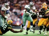 Emmitt Smith (22) runs past Green Bay's Reggie White (92) and Darius Holland during the third quarter of the NFC Championship Game at Texas Stadium in Irving on Jan. 14, 1996.