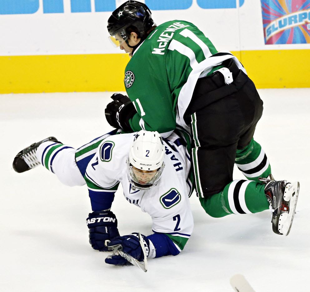 Dallas Stars left wing Curtis McKenzie (11) and Vancouver Canucks defenseman Dan Hamhuis battle for the puck during the first period of their game Tuesday, October 21, 2014 at the American Airlines Center in Dallas, Texas. G.J. McCarthy/The Dallas Morning News) 02272015xSPORTS