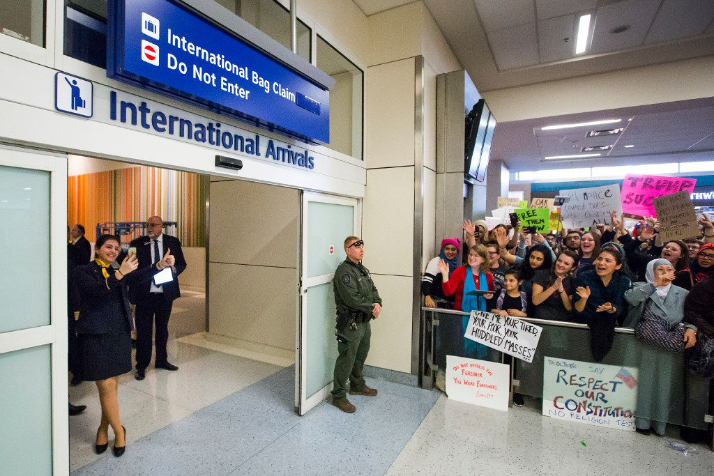 A flight crew member gives a thumbs up to protestors in the international arrivals hall at DFW International Airport gathered in opposition to President Donald Trump's executive order barring certain travelers on Sunday, Jan. 29, 2017.