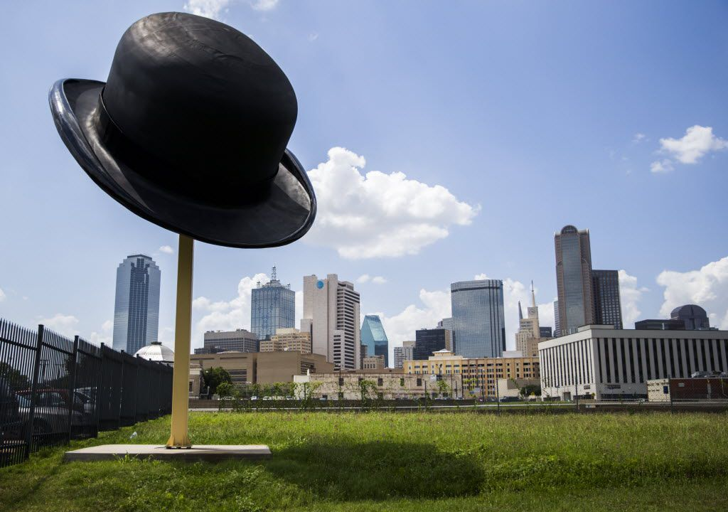 A sculpture of a giant bowler hat by Keith Turman is seen with the Dallas skyline behind it at the intersection of Griffin Street East and South Ervay Street in the Cedars neighborhood.