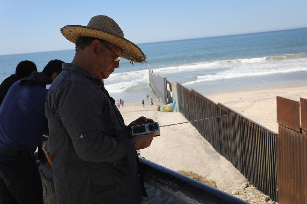 """A man listens to a U.S. radio station while on the Mexican side of the U.S.-Mexico border fence at """"Friendship Park"""" in Tijuana, Mexico. The fence at the park ends in the Pacific Ocean and is one of the few places on the 2,000-mile border where families, many of them separated by deportations, are allowed to meet. (John Moore/Getty Images)"""