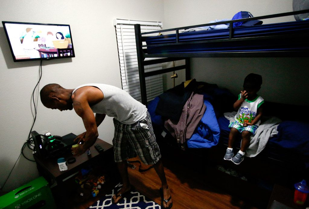 Joshua Miller and his two-year-old son Jordan get ready for the day in their room at The Family Place's men's shelter in Dallas. After weeks of bringing his son along with him for various appointments across the city, Miller prepares his son for his first day of day care. (Tailyr Irvine/The Dallas Morning News)