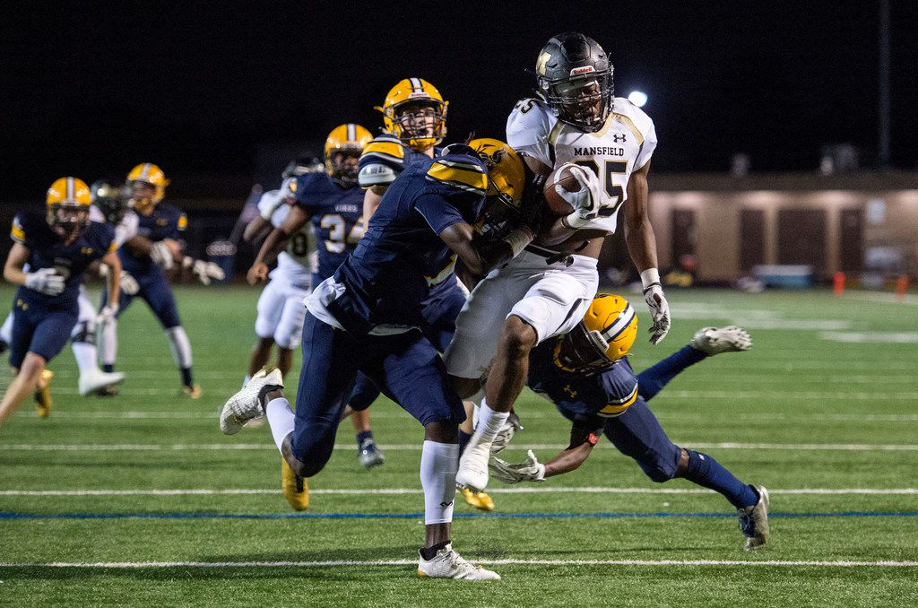 FILE - Mansfield senior running back Jaqulis Coleman (25) is hit by Arlington Lamar defensive backs Deshawn Gaddie (1), left, and Califa Garr (6) as he crosses the goal line for the first touchdown of a high school football game on Friday, October 20, 2017 at Cravens Field in Arlington, Texas. (Jeffrey McWhorter/Special Contributor)