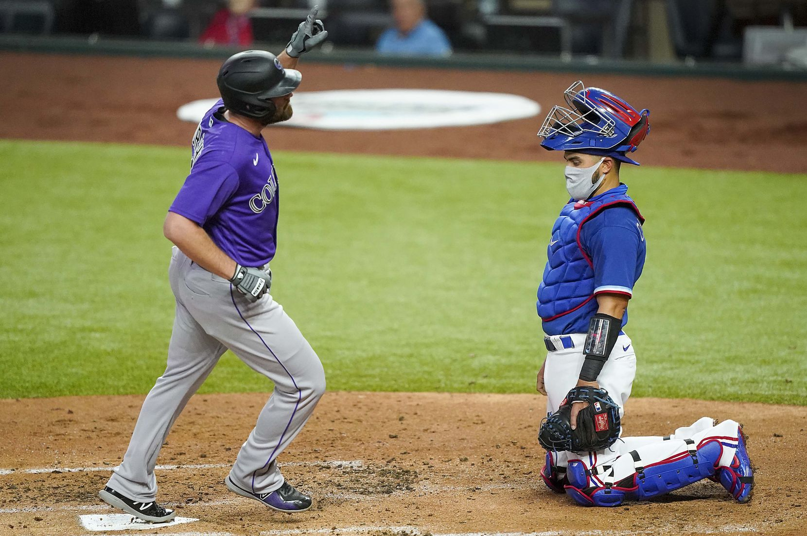 Texas Rangers catcher Robinson Chirinos watches as Colorado Rockies first baseman Daniel Murphy celebrates while crossing home after hitting a solo home run during the second inning of an exhibition game at Globe Life Field on Tuesday, July 21, 2020.