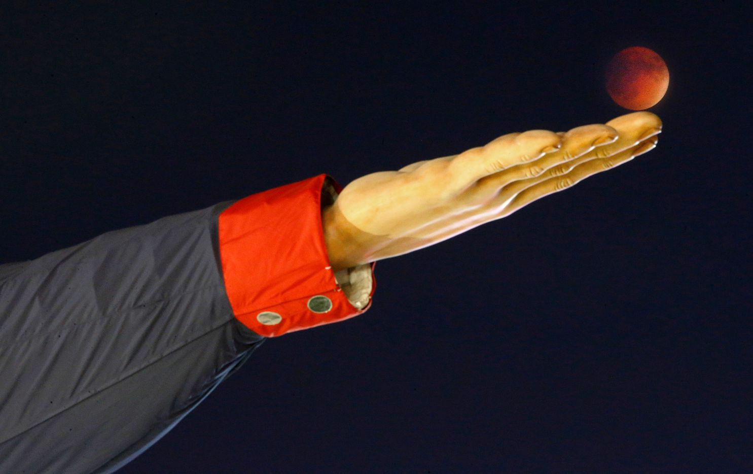 Big Tex appears to be balancing the Super Blood Moon on his fingertips during a lunar eclipse on Sept. 27, 2015 during the State Fair of Texas at Fair Park in Dallas. When the moon enters the umbra or darker inner shadow, the total eclipse begins and the moon appears reddish orange.