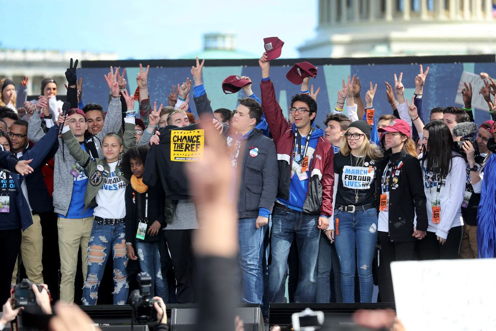 At the end of the rally, Marjory Stoneman Douglas students wave to the crowd during March for Our Lives to demand stricter gun control laws on Saturday in Washington, D.C. (Mike Stocker/Sun Sentinel/TNS)