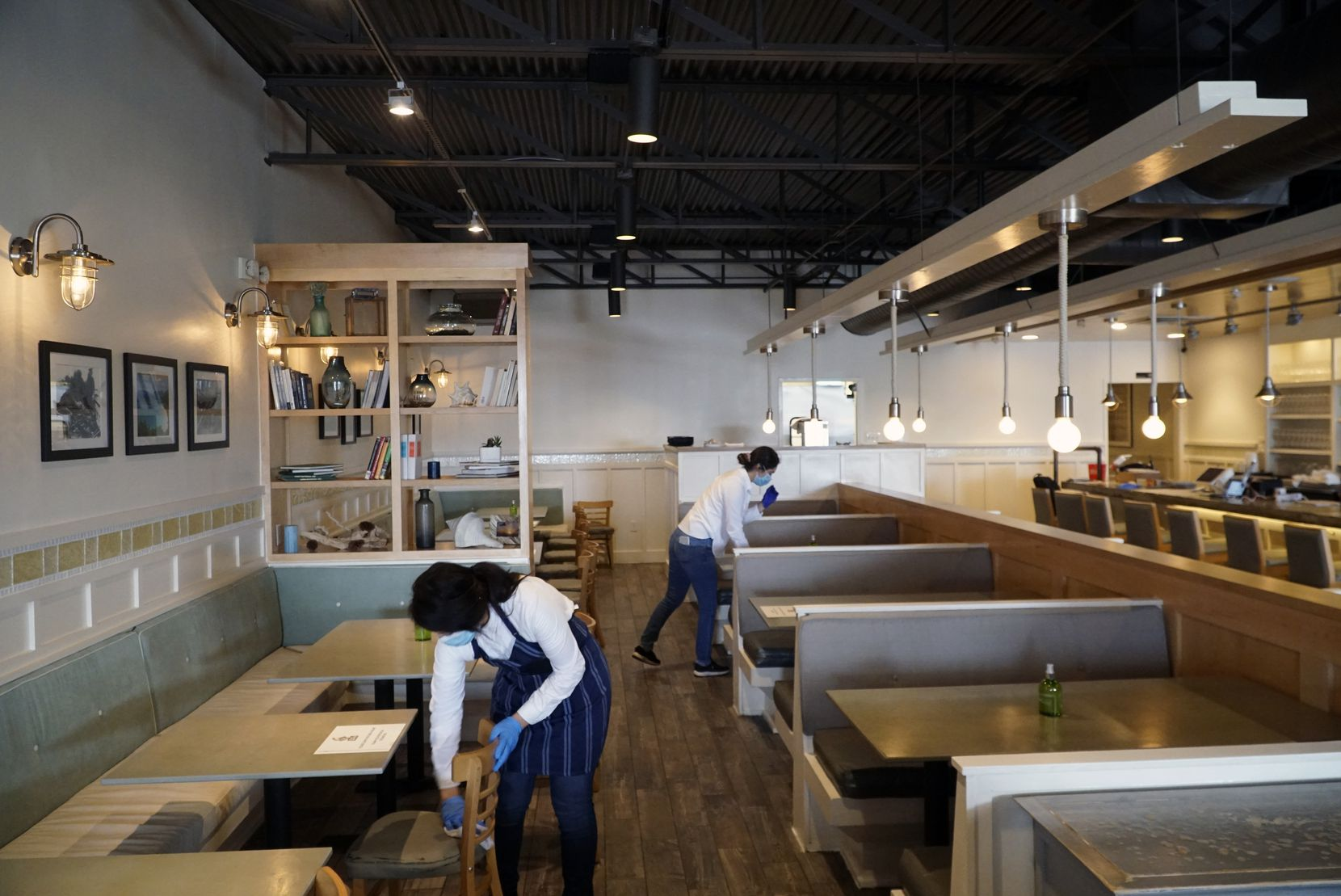 TJ's Seafood employees clean chairs and tables in preparation for reopening the inside to the public at the restaurant in Dallas, Texas on Friday, May 15, 2020. Every other table will be used for social distancing and hand sanitizer will be at each table.