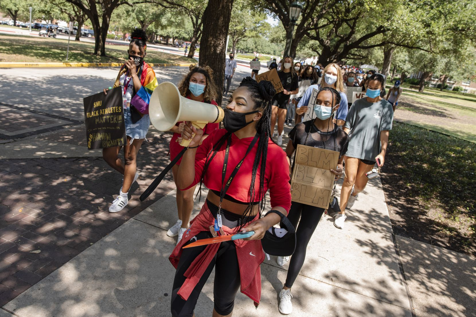 """Track and field athlete Brooke Shepherd, center, uses a megaphone to chant, """"no justice! No peace!"""" during a Black Lives Matter movement march conducted by SMU Black student athletes on the campus in Dallas, Aug. 28, 2020. (Ben Torres/Special Contributor)"""