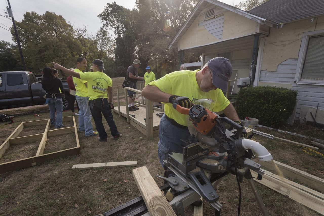 Gary Stopani (foreground), along with other volunteers with the Texas Ramp Project, builds a wheelchair ramp Saturday for a disabled man in a South Dallas neighborhood. The Richardson-based organization has built over 10,000 ramps in the state.