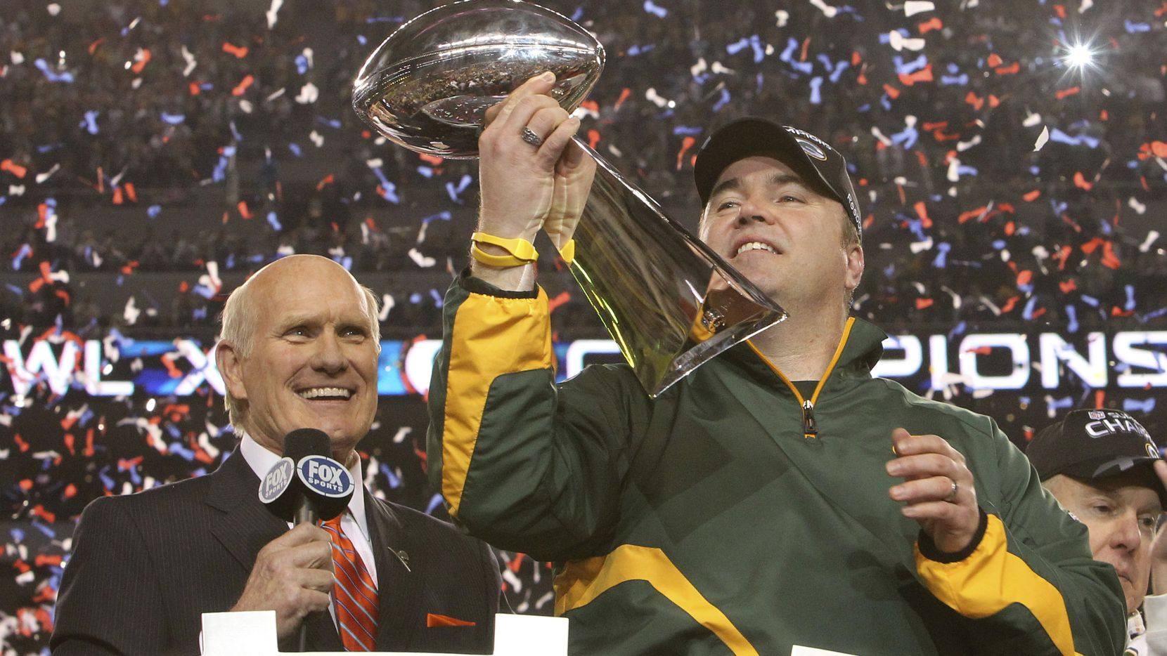 Green Bay Packers head coach Mike McCarthy admired the Lombardi Trophy as Terry Bradshaw looks on after Super Bowl XLV at Cowboys Stadium in Arlington, Texas, on Sunday, February 6, 2011. Green Bay won the game 31-25.