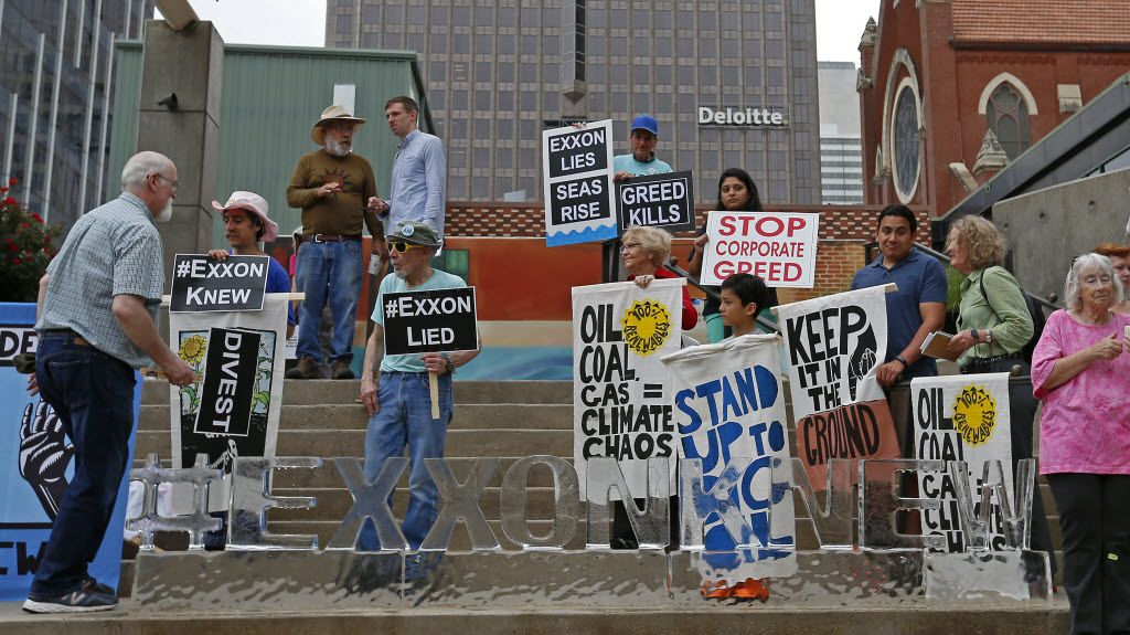 People protest across from the Morton H. Meyerson Symphony Center where the Exxon Mobil annual shareholder meeting was held in Dallas, Wednesday, May 25, 2016.