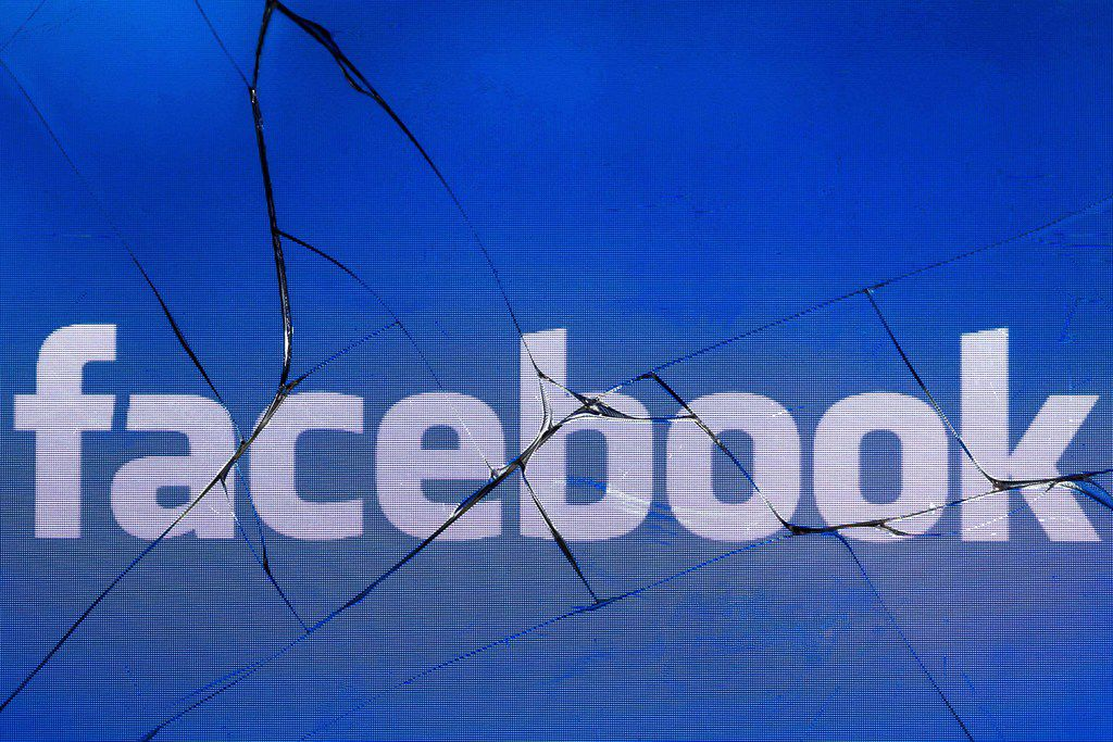 In this file photo taken on May 16, 2018 in Paris shows the logo of the social network Facebook on a broken screen of a mobile phone.