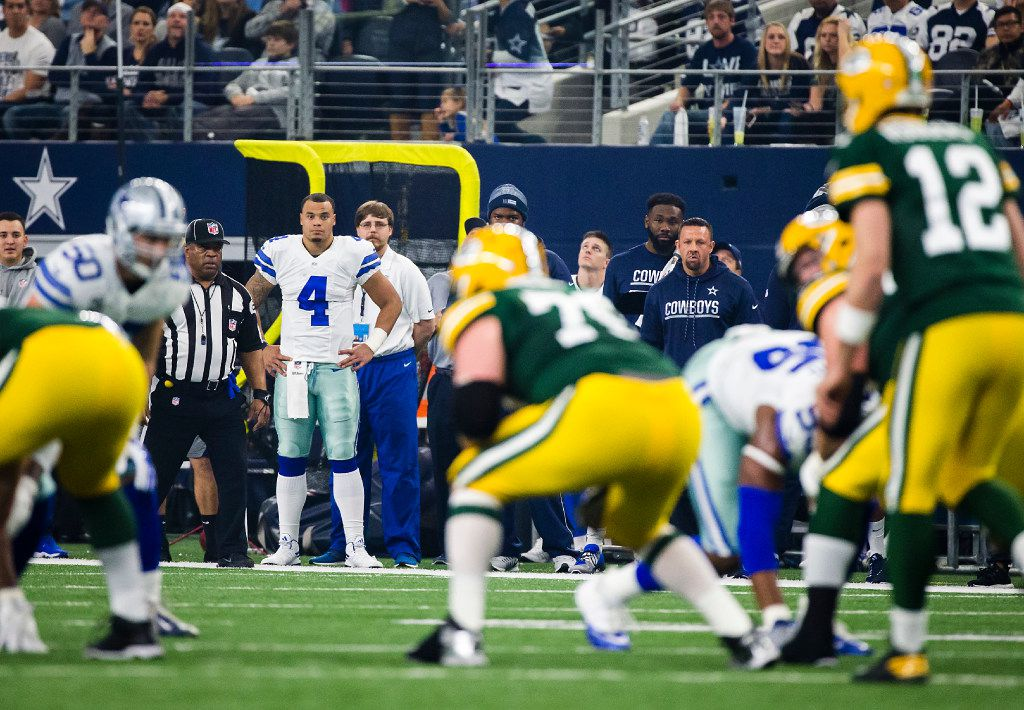 Dallas Cowboys quarterback Dak Prescott (4) watches from the sidelines as Green Bay Packers quarterback Aaron Rodgers (12) brings his team to the line of scrimmage during the first half of an NFC divisional round playoff game at AT&T Stadium on Sunday, Jan. 15, 2017, in Arlington.