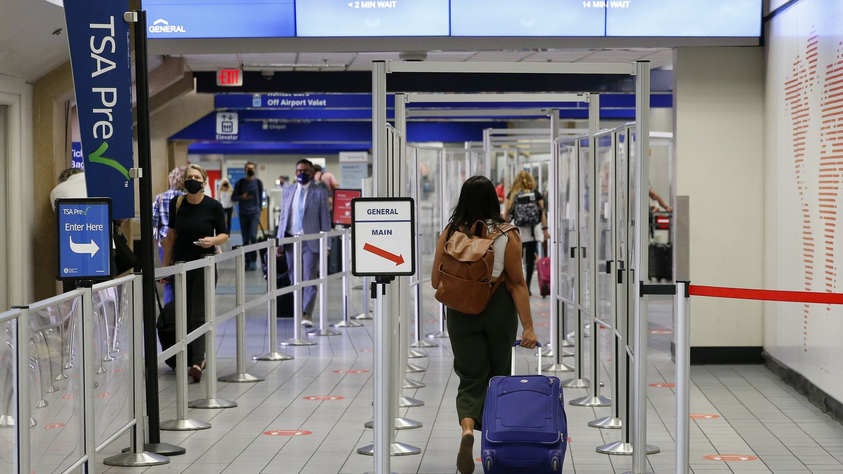 Travelers make their way to a security checkpoint at DFW International Airport.