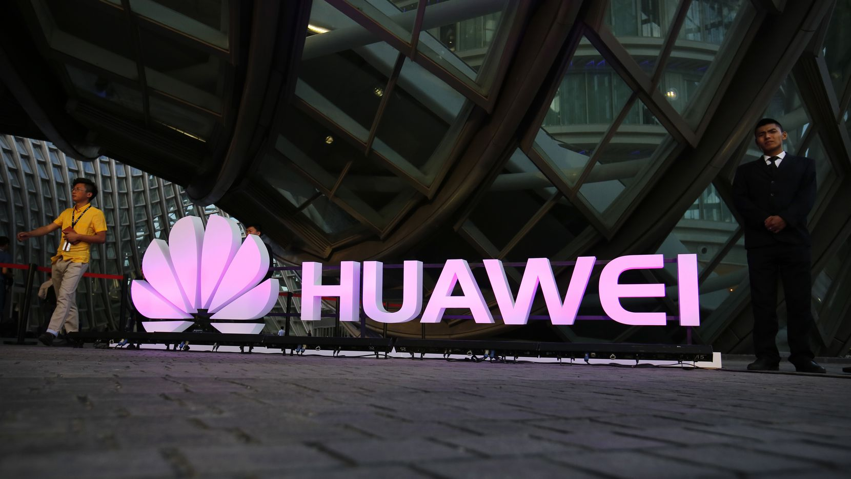 People walk past an illuminated logo for Huawei at a launch event for the Huawei MateBook in Beijing, Thursday, May 26, 2016. Chinese tech company Huawei officially launched the 2-in-1 notebook computer on Thursday, which aims to compete against devices such as the Microsoft Surface and iPad Pro. (AP Photo/Mark Schiefelbein)