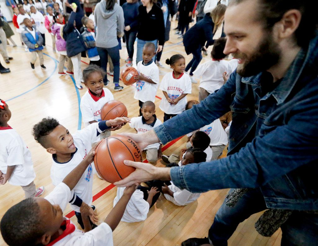 Tyler Shafer with Looney and Associates ( right, hands out a basketball to excited students at JW Ray Elementary School in Dallas, Thursday, December 8, 2016. The interior design firm raised money and donations to help redecorate two teacher lounges, provide a new laundry washer and dryer, school supplies and sports equipment.